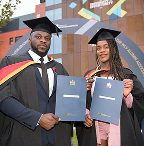 Two students proudly holding their degree certificates while wearing their cap and gowns.