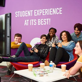 image of a group of students sitting watching 2 others play on a games console
