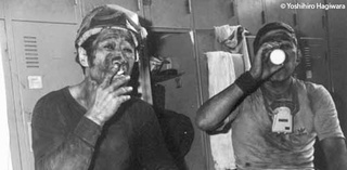 Two Japanese Miners sitting next to each other - one smoking the other drinking a coup of tea.