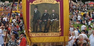 Halswell Lodge banner at Miners' Gala.  The banner has three male figures and says 'They being dead yet speaketh'.  Behind the banner are crowds of people at the gala